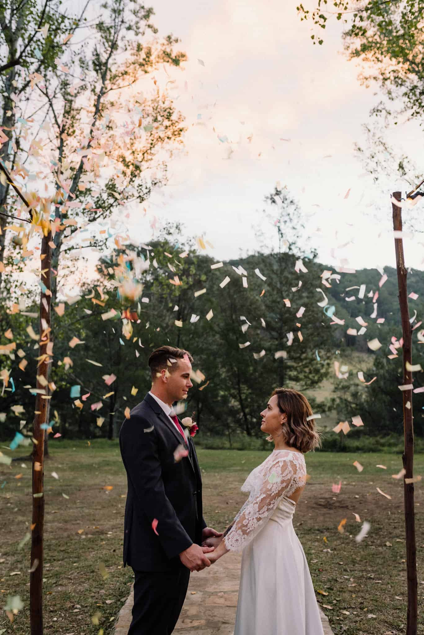 gorgeous bride and groom holding hands as the sun sets behind them and confetti pours down from the sky at stonehurst cedar creek james white hunter valley wedding photographer