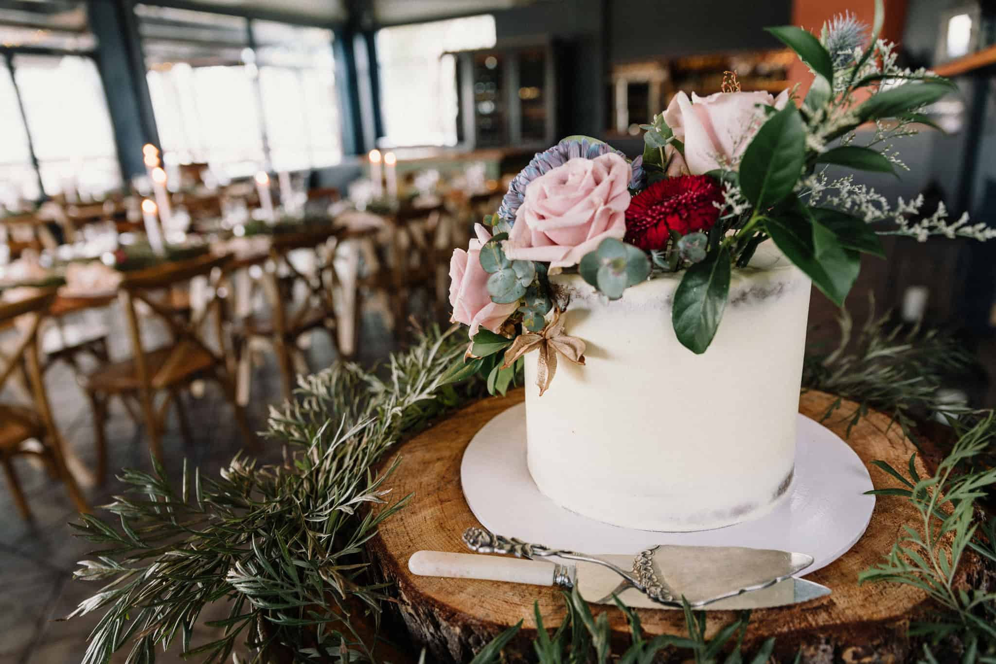 Semi naked floral wedding cake ready to cut in the mill restaurant at Estate Tuscany Captured by James White Hunter Valley Wedding Photographer
