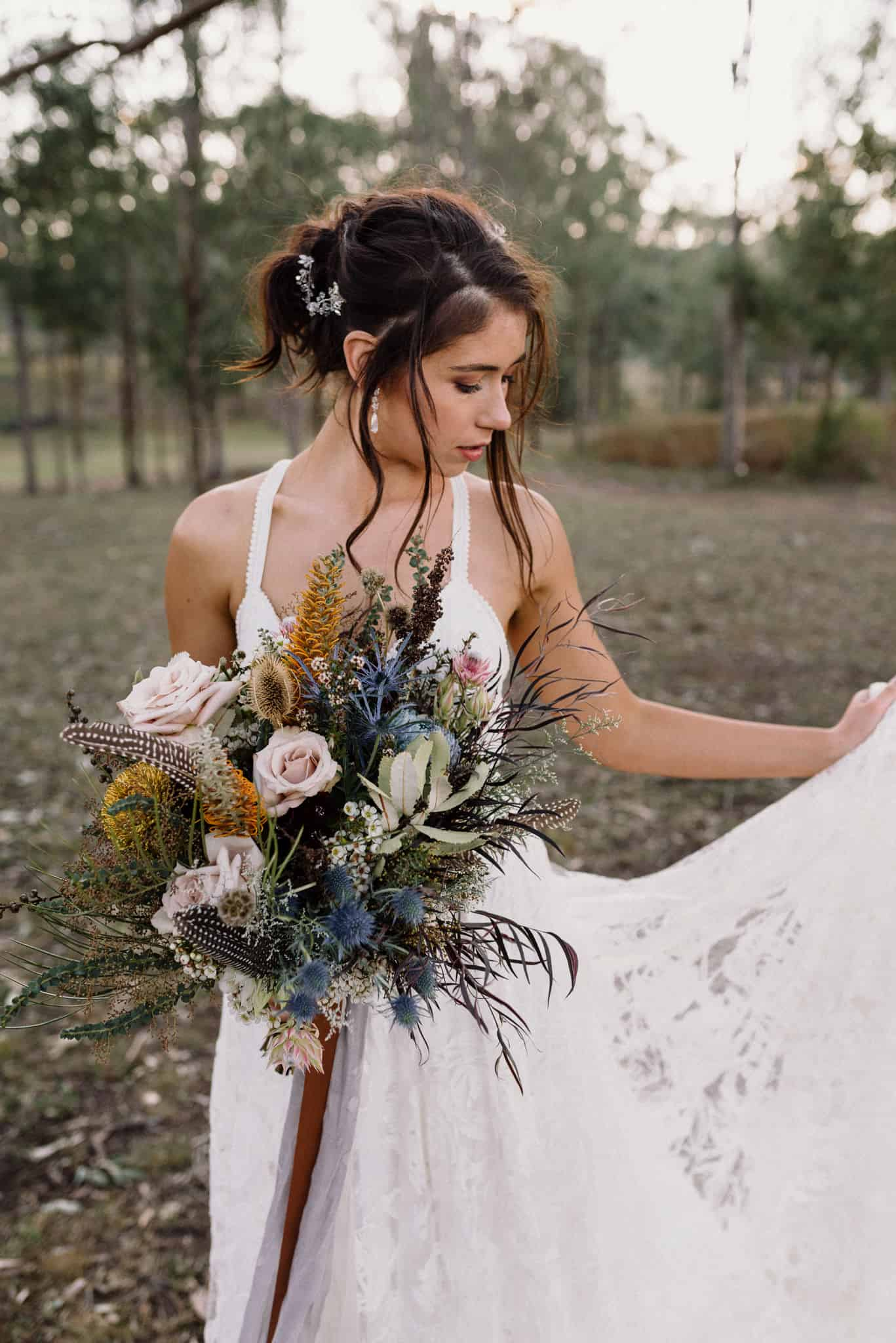 Bride portrait in the grounds of Estate Tuscany Bride playing with dress train while holding bouquet Captured by James White Hunter Valley Wedding Photographer
