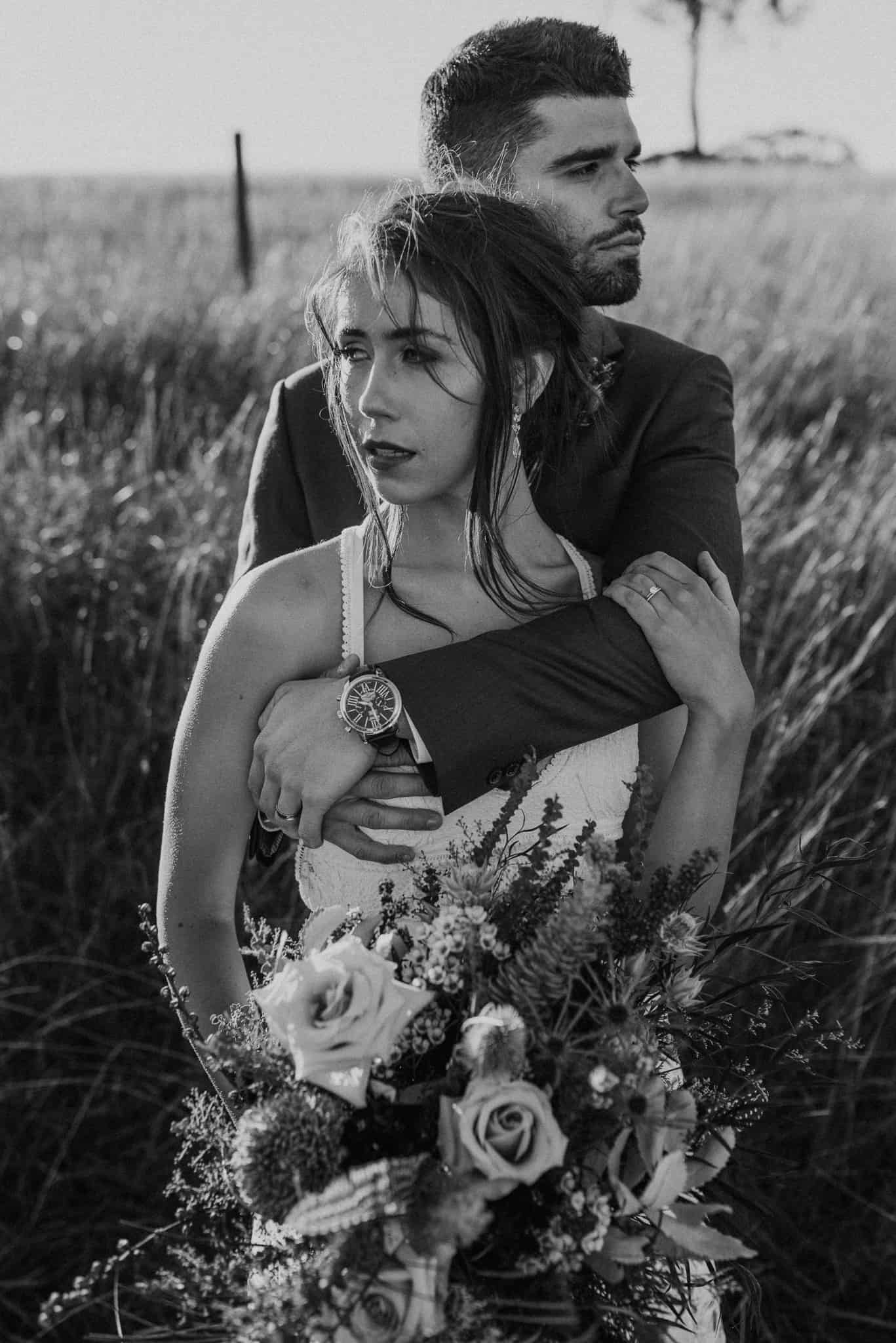 Bride and groom stand in tall grass outside venue at Estate Tuscany Captured by James White Hunter Valley Wedding Photographer