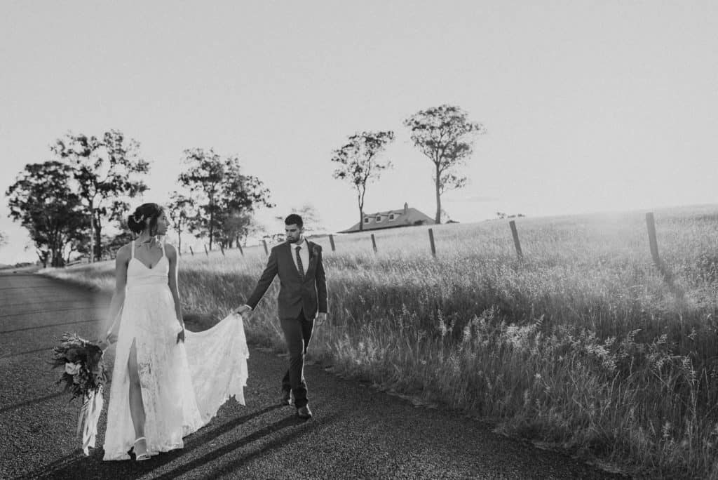 bride and gro walk down country road outside estate tuscany as sun sets over the fields captured by james white hunter valley wedding photographer