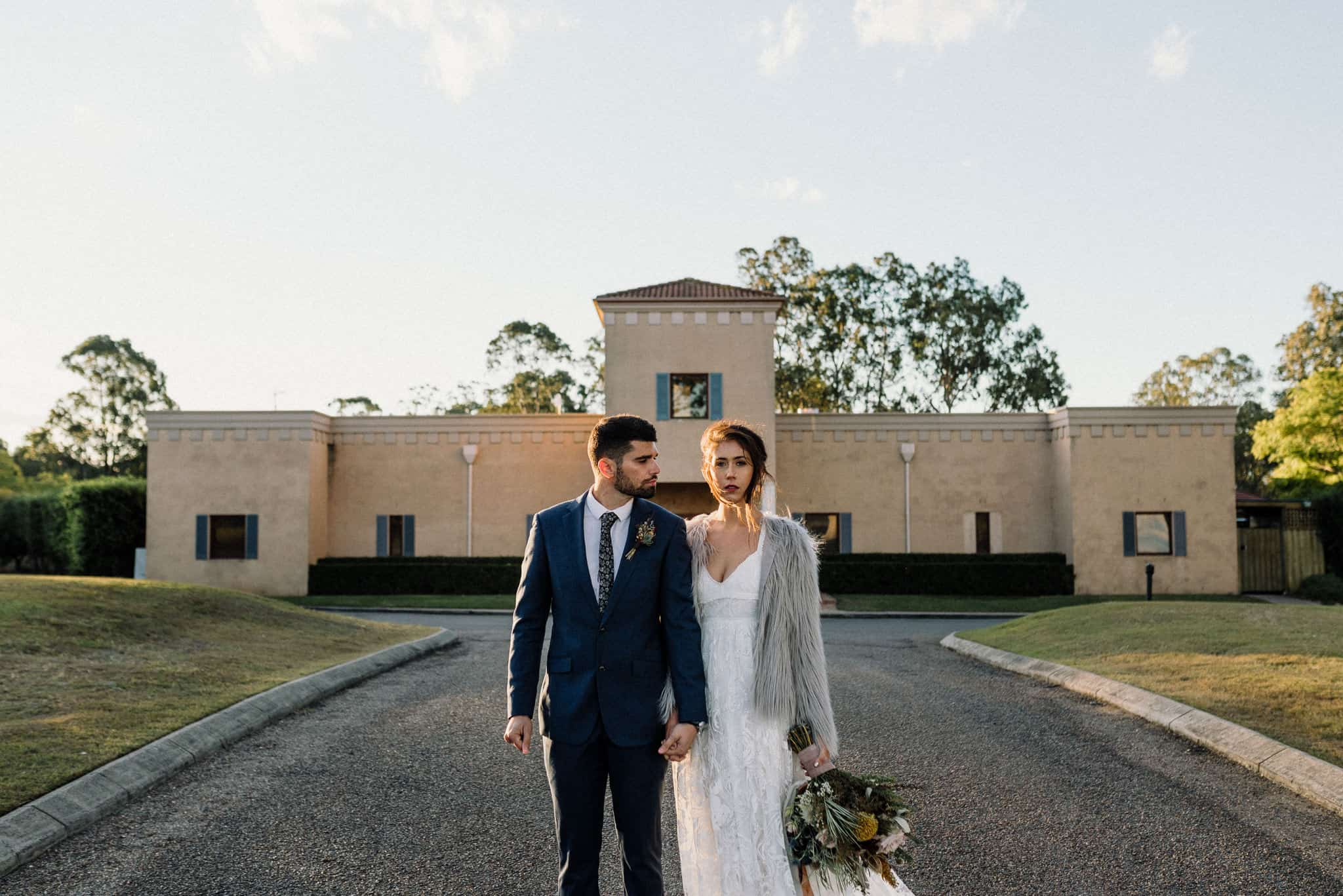Newlyweds stand outside entrance to Estate Tuscany Captured by James White Hunter Valley Wedding Photographer