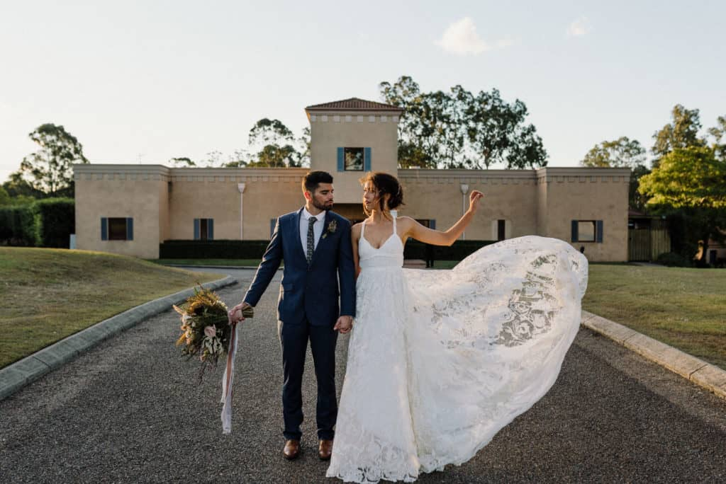 bride and groom stand in front of iconic estate tuscany villa as bride throws dress in the wind, captured by hunter valley wedding photographer james white