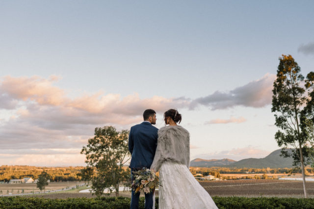 bride and groom stop and stare out ove the vineyards and mountains as he sun sets at estate tuscany capted by james white hunter valley wedding photographer