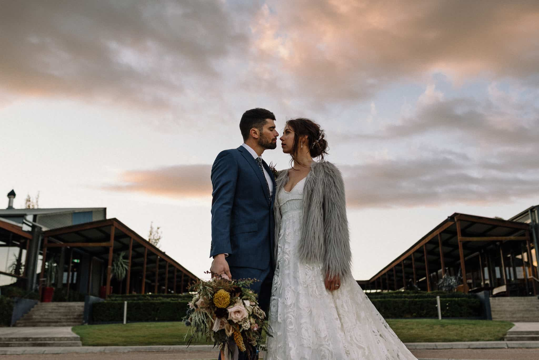 Newlyweds stand in front of courtyard at Estate Tuscany Captured by James White Hunter Valley Wedding Photographer