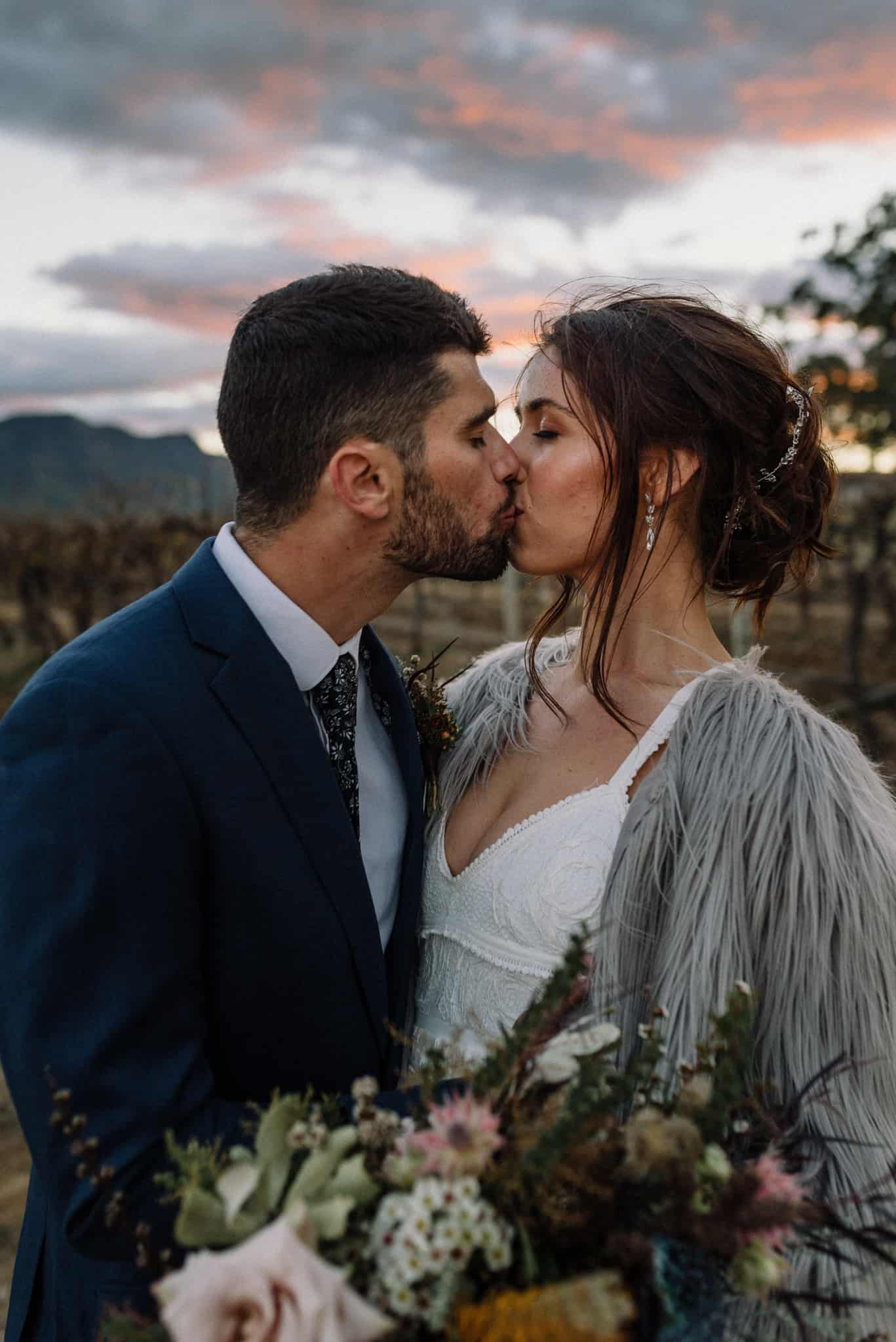 Newlyweds kissing in the vines at Estate Tuscany as sun goes down Captured by James White Hunter Valley Wedding Photographer
