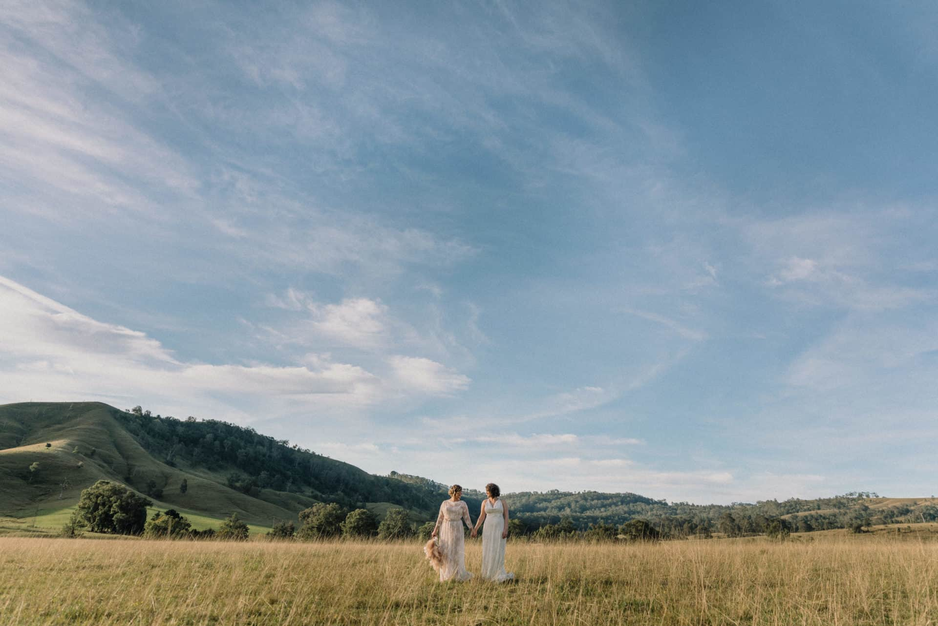 two brides embracing in a golden field under the Australian sun at Lynwood hunter valley wedding venue favourite