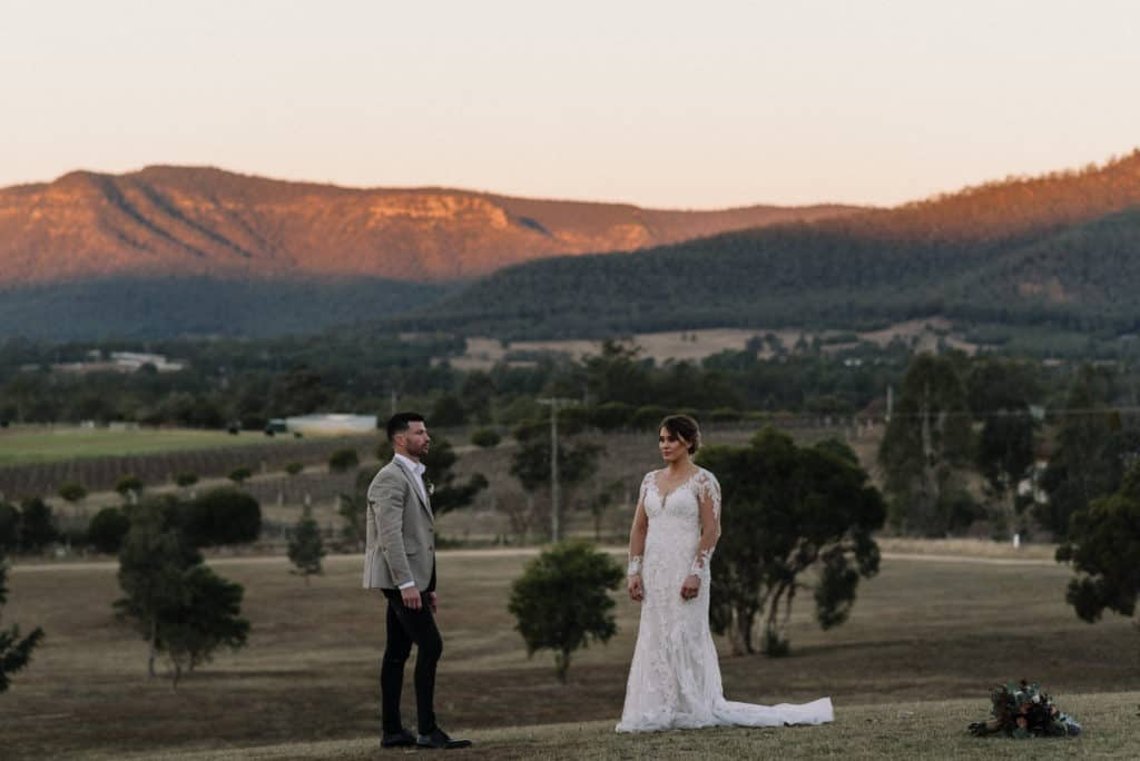 bride and groom stand against mountains backdrop on wedding day at adams peak