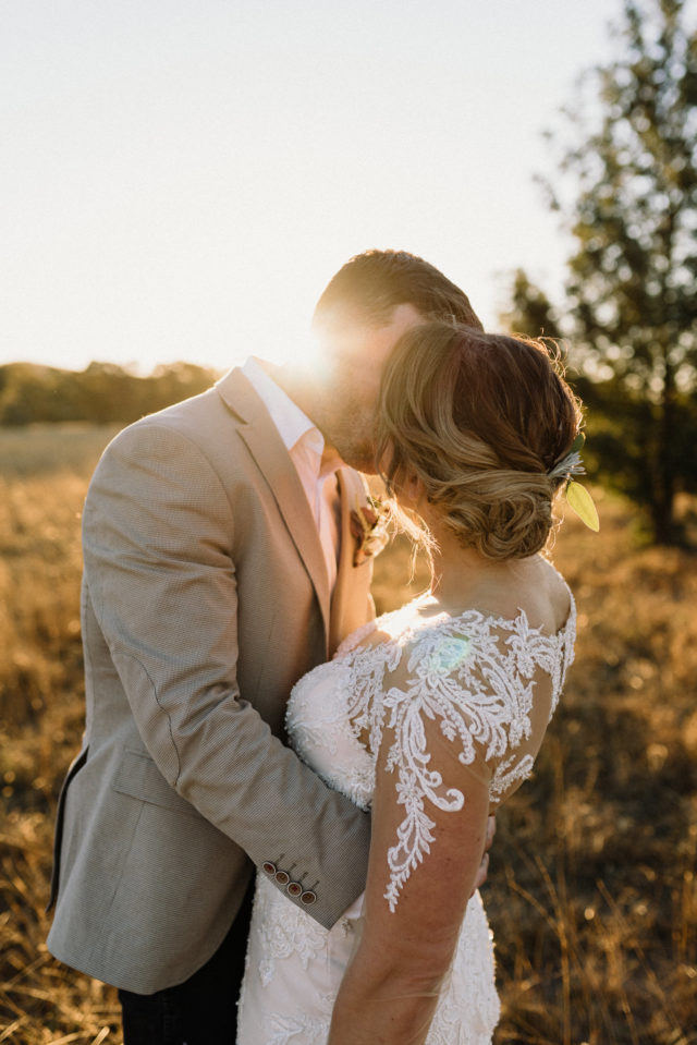 bride and groom share first kiss right as the sun sets behind them covering them in gorgeous golden light - wedding planning is about getting a timeline right