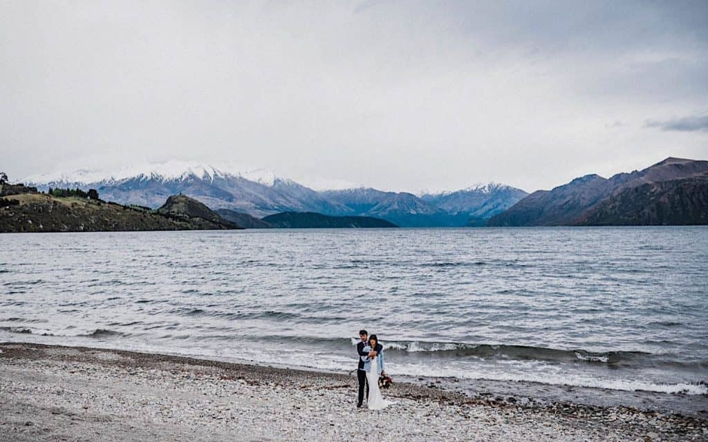 bride and groom standing on black sand beach on new zealand after saying their own personal wedding vows
