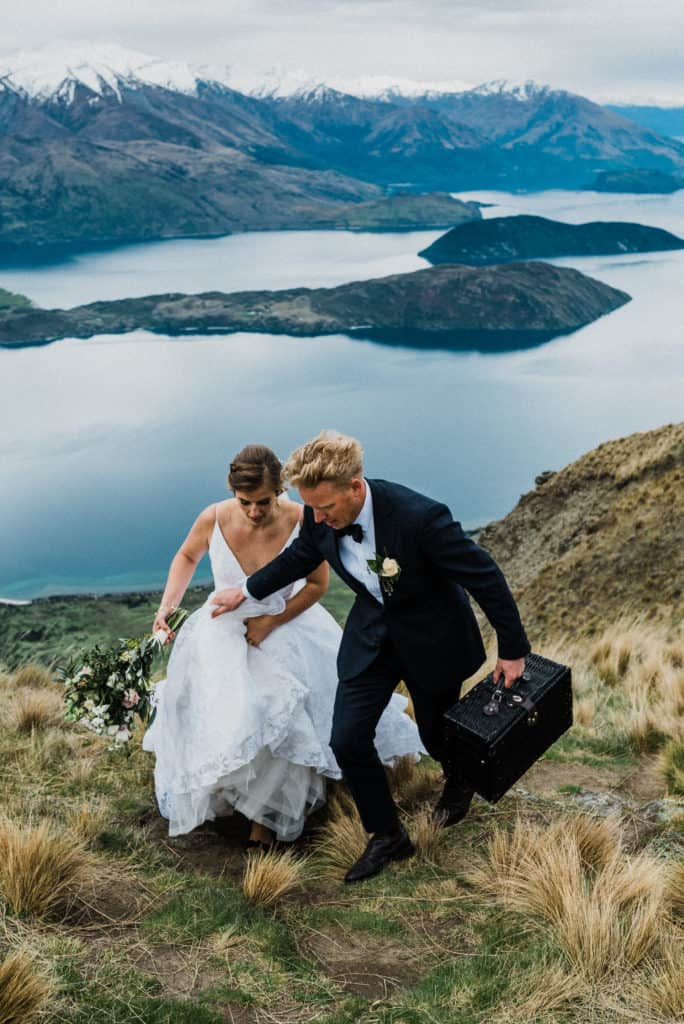 Bride and groom hike up New Zealand mountainside in Wanaka carrying a picnic for after elopement ceremony.