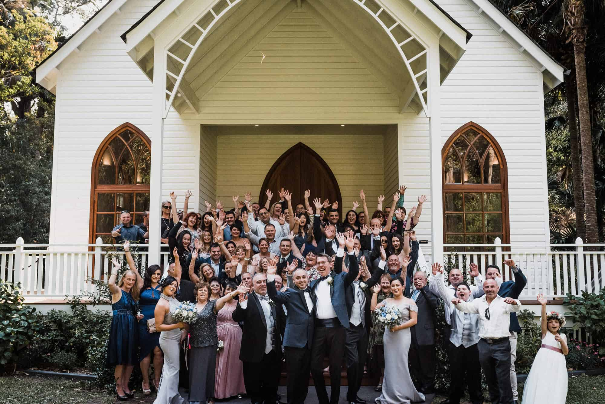 wedding party cheer for group photo outside kintara house chapel