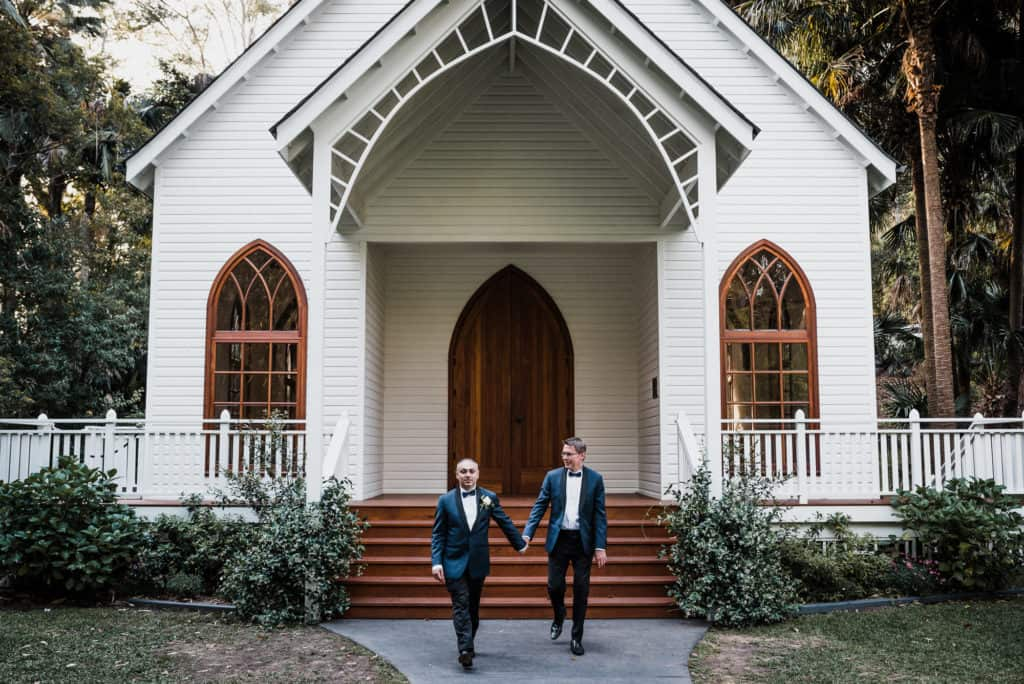 two grooms hold hands in front of vintage chapel at Kantara House