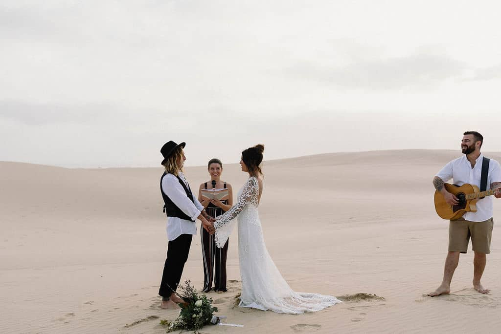bride and groom stand on top of Stockton sand dunes as acoustic guitarist plays during their ceremony