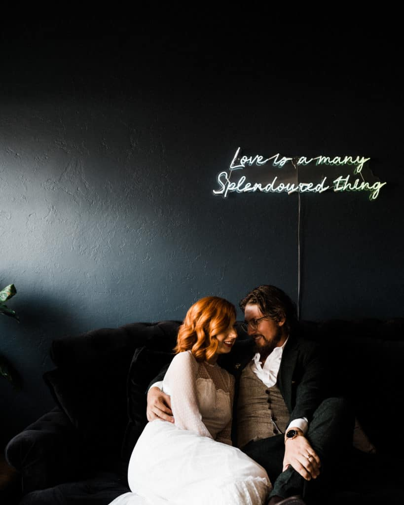 bride and groom kiss on vintage couch in gorgeous lighting savoy long jetty wedding