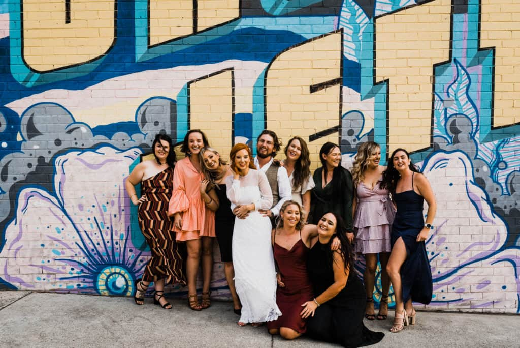 The girls at the wedding with bride and groom outside against graffiti wall savoy long jetty wedding