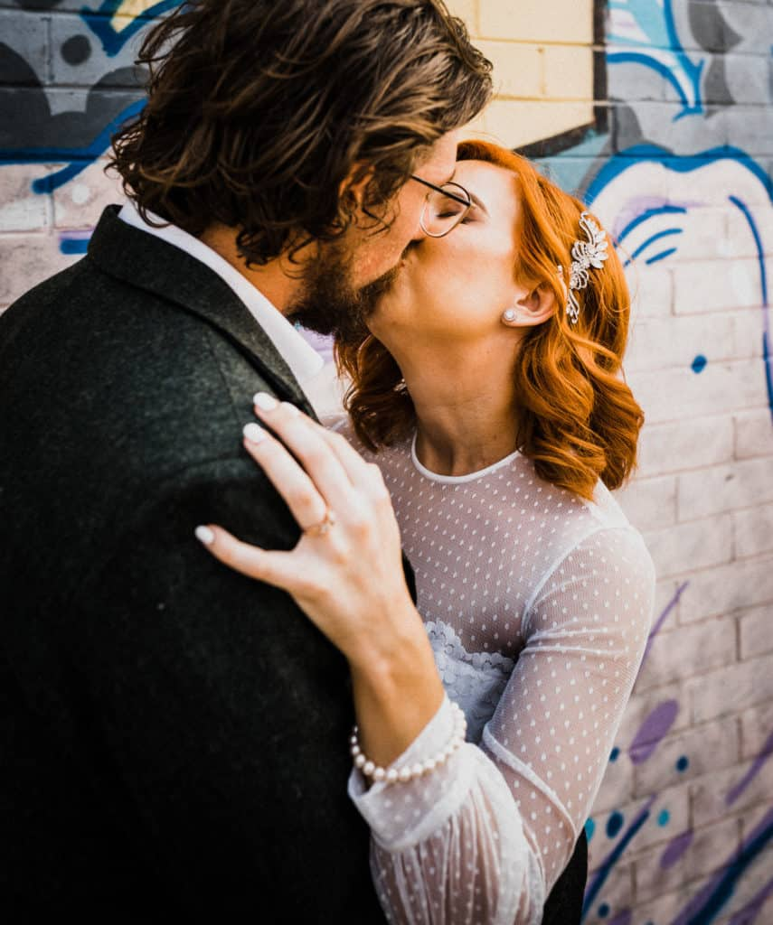 bride and groom share a kiss against graffiti wall in long jetty the savoy long jetty wedding