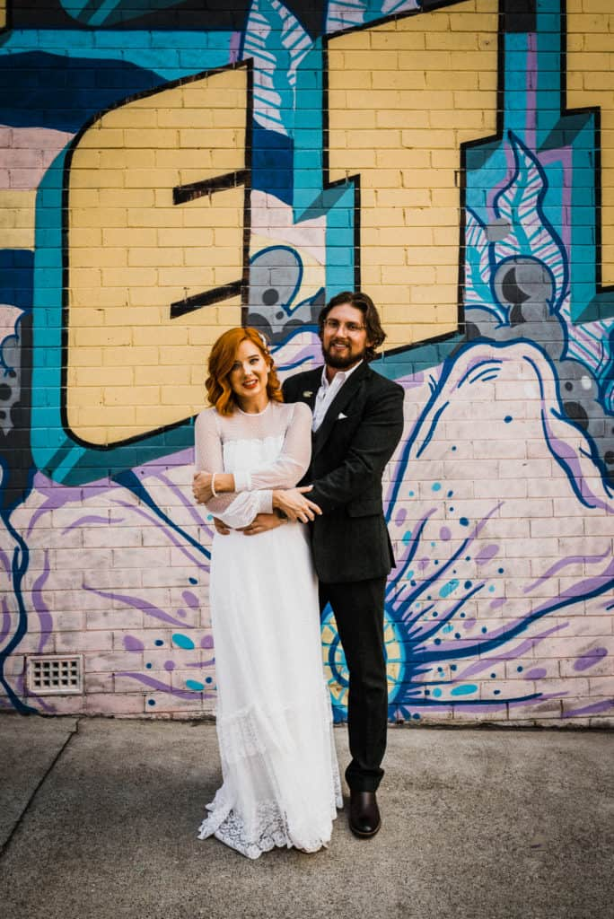 bride and groom pose against graffiti wall in long jetty the savoy long jetty wedding