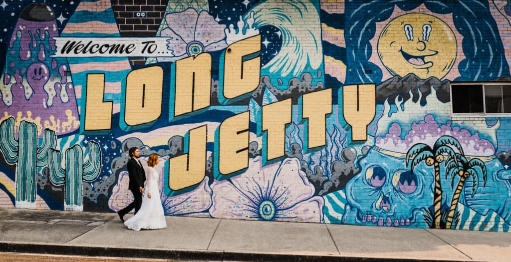 bride and groom walk down the street against graffiti wall in long jetty the savoy long jetty wedding