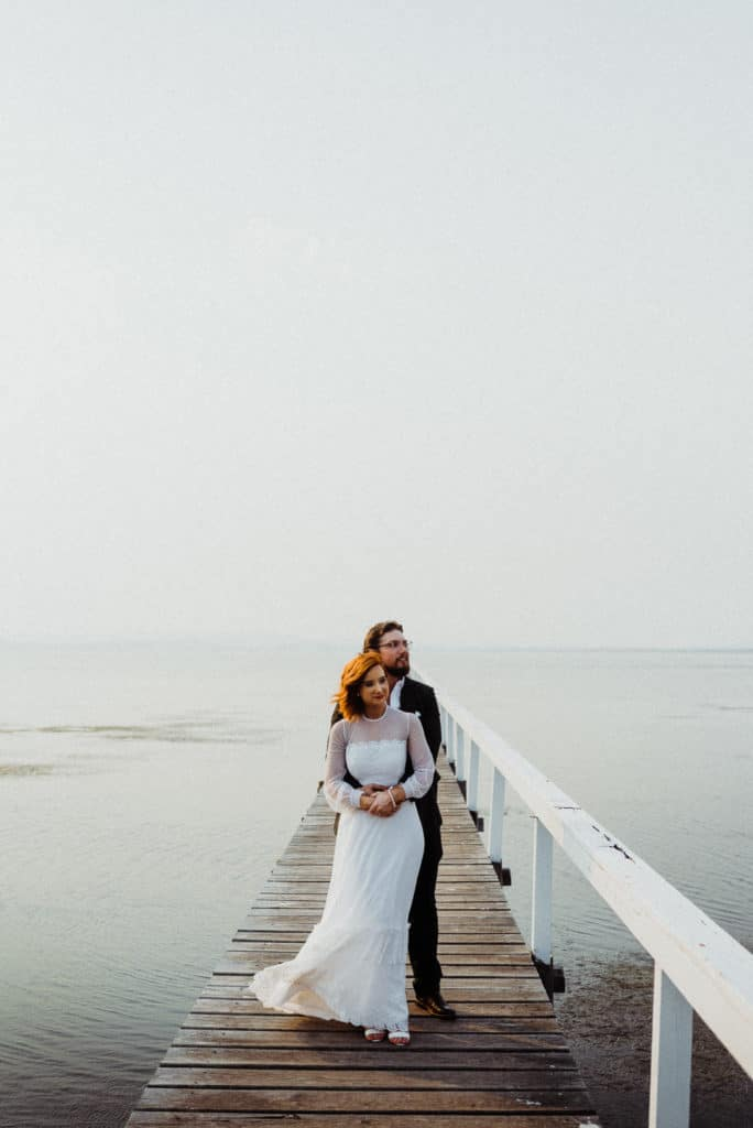 bride and groom posing for epic portraits on the jetty on the lake at the savoy long jetty wedding