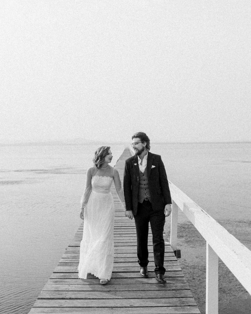 bride and groom walking along the jetty on the lake at the savoy long jetty wedding