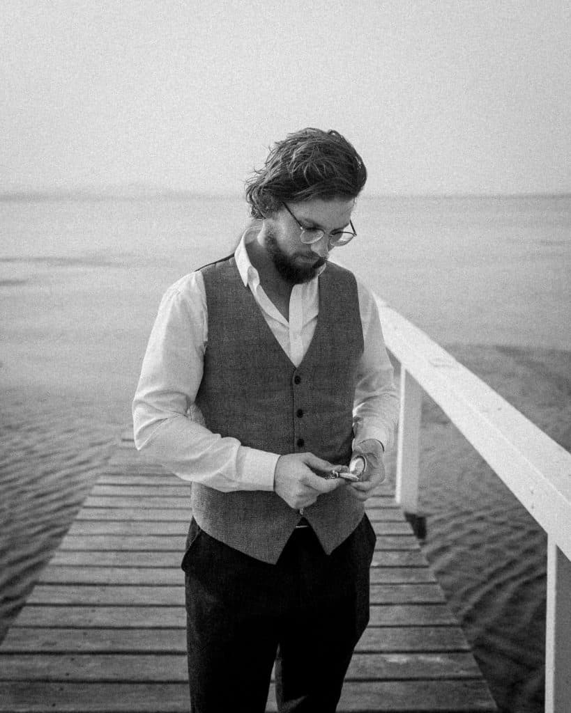 groom checking pocket watch on the lake at the savoy long jetty wedding