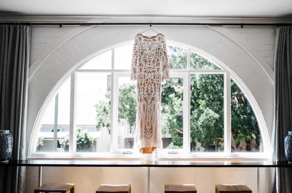 beautiful wedding dress hanging in window of gorgeous brick room
