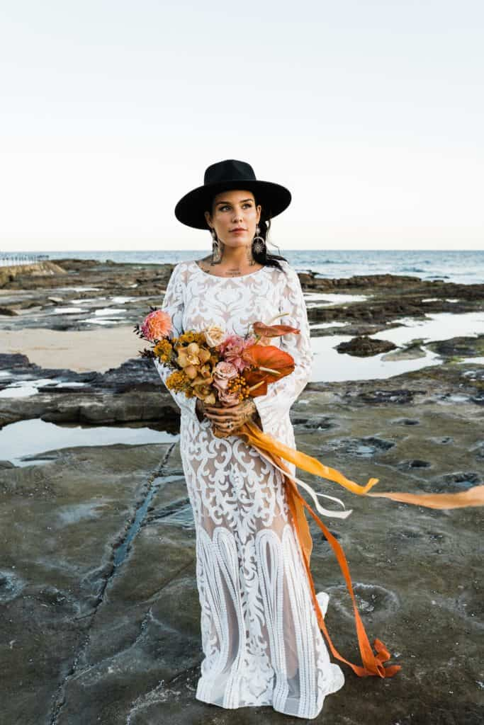 gorgeous bride with stunning floral arrangement stands on rocks at Newcastle beach under sunset