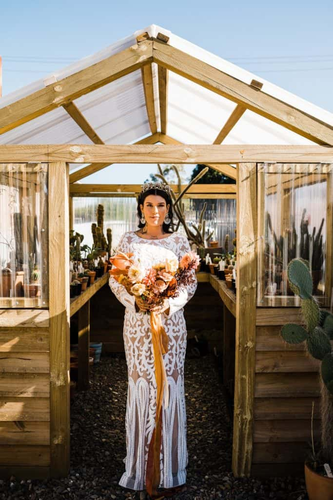 bride posing in front of cactus greenhouse before wedding ceremony in Newcastle