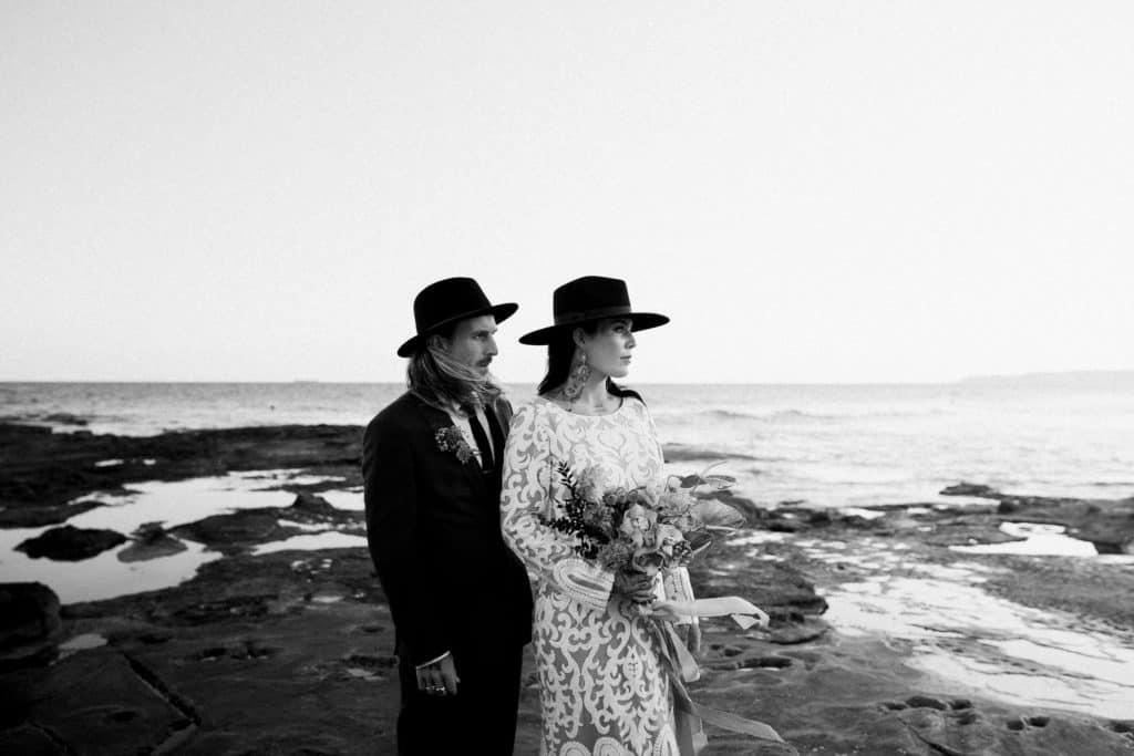 Bride and groom standing against the ocean as they elope | forgetting all about wedding day traditions