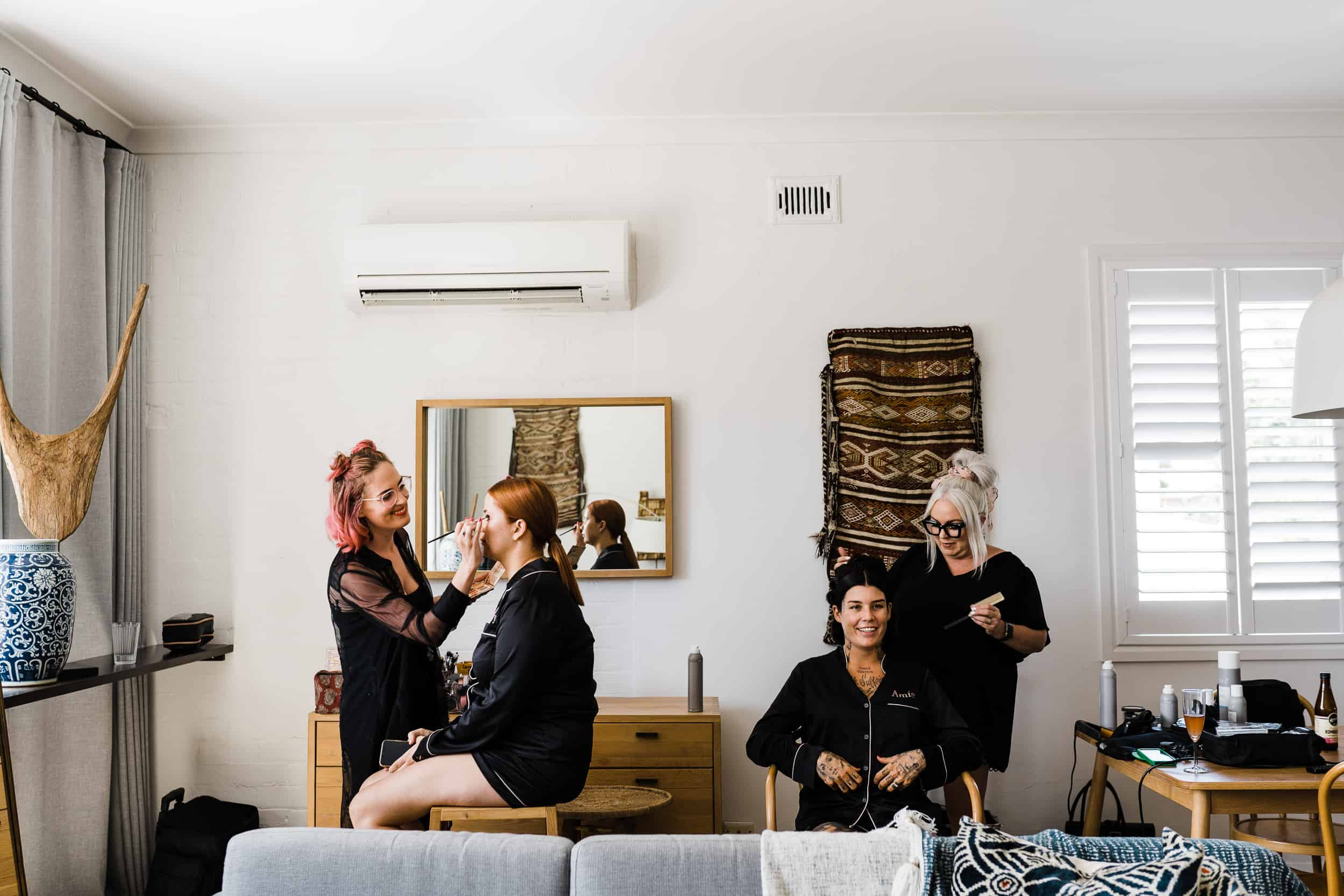 best wedding vendors in Newcastle doing hair and makeup on bride and bridesmaid
