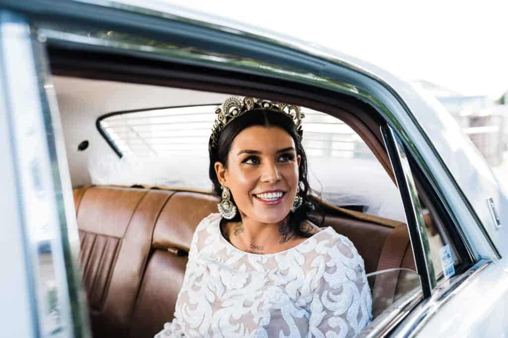 gorgeous tattooed bride getting out of wedding car before ceremony