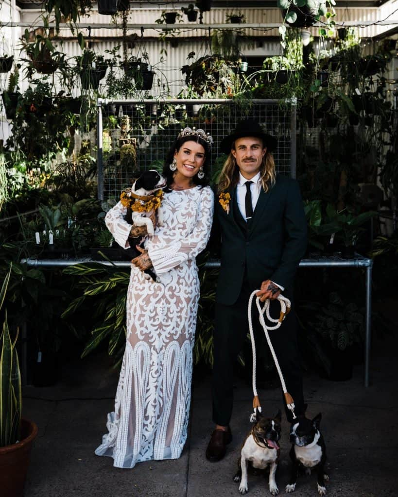 bride and groom posing in plant store with cute dogs after wedding ceremony
