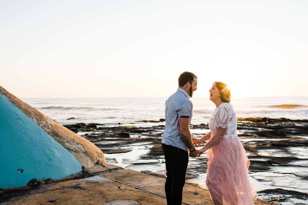bride and groom laughing on the rocks at newcastle bath under the sun rising captured by james white newcastle wedding photographer