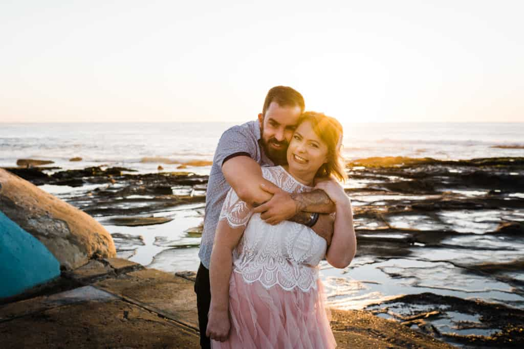 beautiful shot of bride and groom posing against the ocean and rockpool captured by james white newcastle wedding photographer