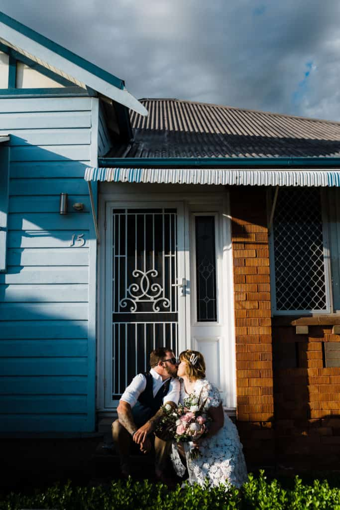 bride and groom sit on step out front of their home before they leave for wedding captured by james white newcastle wedding photographer