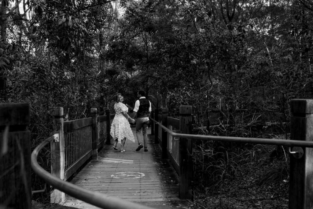 bride and groom walking down the trail to elopement spot at Glenrock captured by james white newcastle wedding photographer