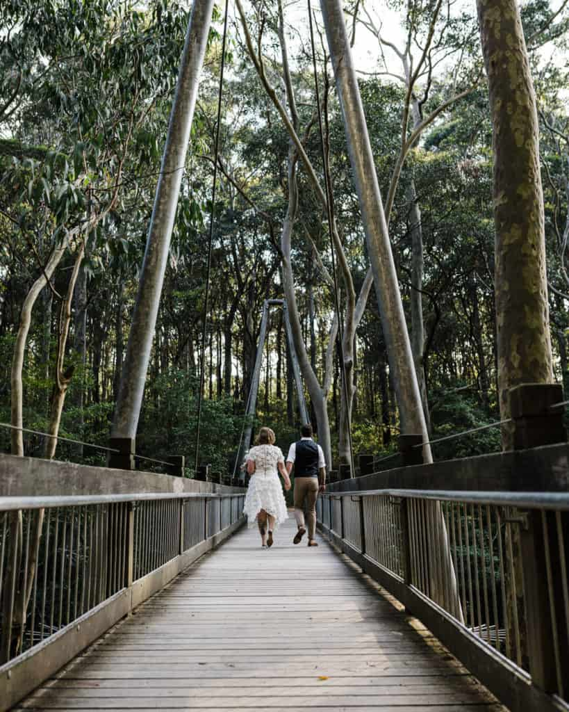 bride and groom walk over bridge to elopement ceremony spot at Glenrock captured by james white newcastle wedding photographer
