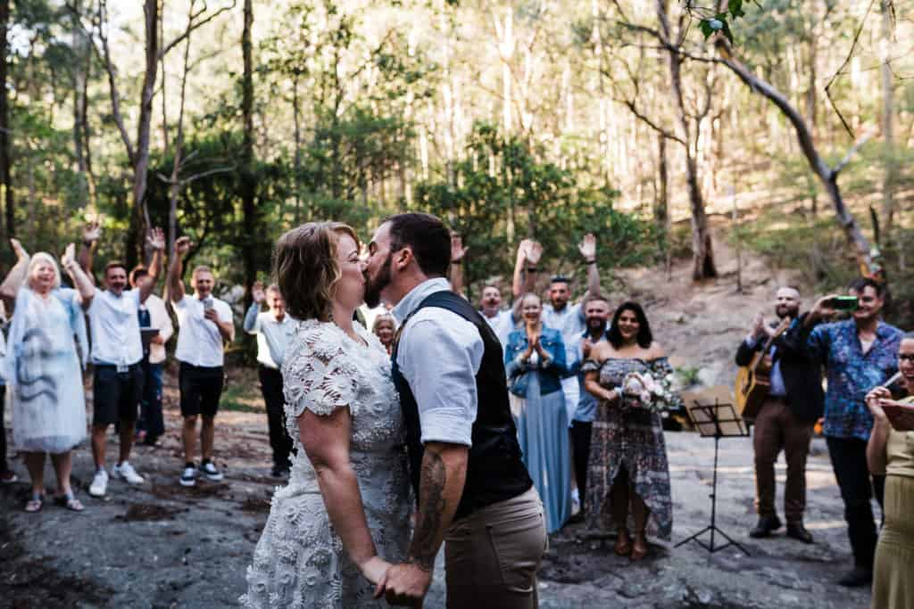 Bride and groom have first kiss in front of friends and family at Glenrock captured by james white newcastle wedding photographer