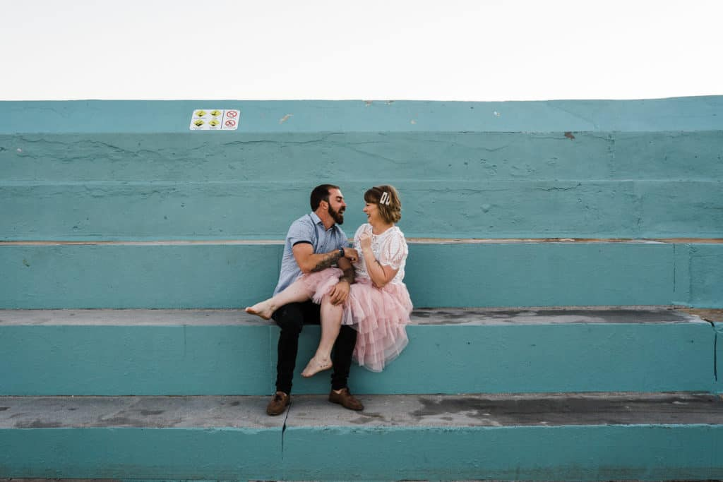 bride and groom sitting on blue steps at newcastle baths captured by james white newcastle wedding photographer