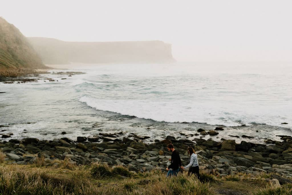 Casually dressed bride and groom walk along the rocky beach on a misty, foggy day in Australia