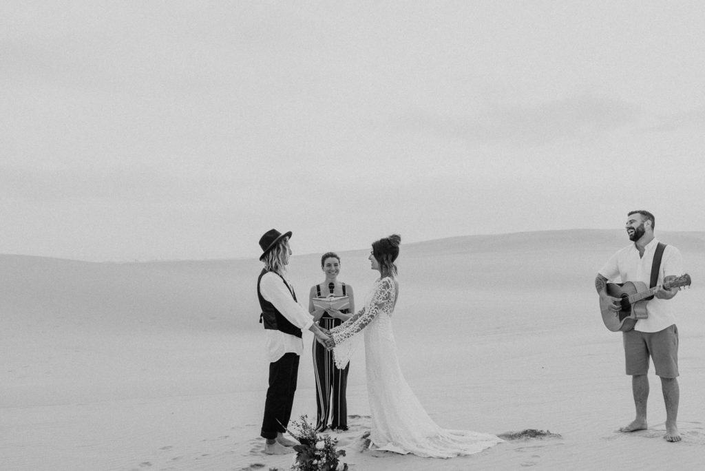 Elopement ceremony, best place to sloep at stockton sand dunes. Couple share wedding vows