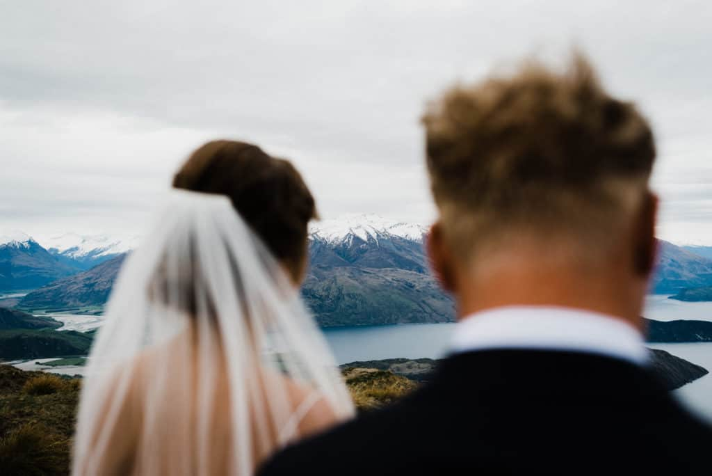 Shot of Coronet Peak through silhouette of bride and groom after elopement ceremony on Roys Peak.