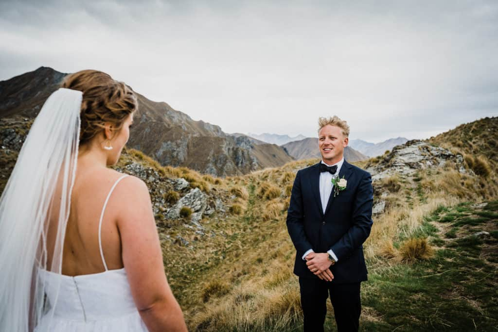 Bride and groom say vows to each other on top of New Zealand mountains. Celebrant helped how to write vows