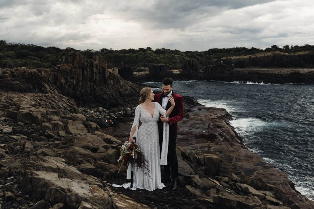 bride and groom pose on a clifftop overlooking the ocean, no wedding day traditions