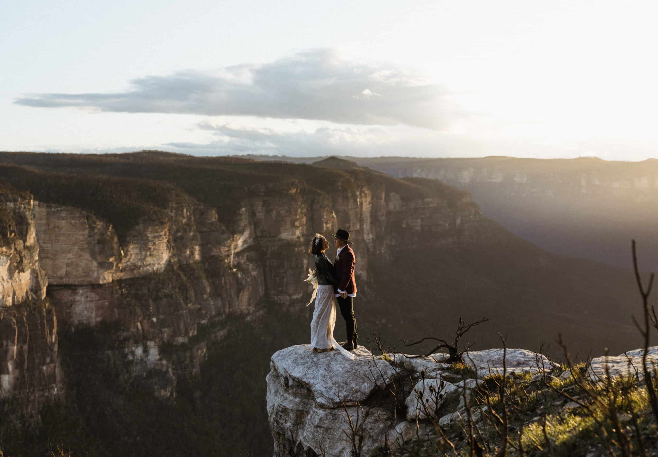 bride and groom sunset portraits on edge of the cliff in the mountains in NSW after elopement
