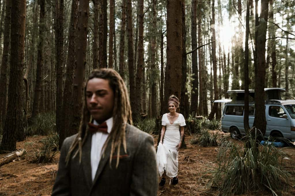 Bride and groom do a first look, despite the wedding day traditions in the pine forest before wedding ceremony